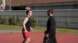 Two men guys having fun on a street basketball ground
