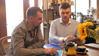 Two Men use a Digital Tablet on a Business Lunch in Cafe