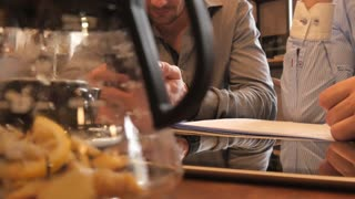 Two Men use a Mobile Smartphone on a Business Lunch in Cafe