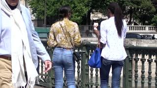 Two women african-american eating Ice Cream walking on Bridge of Paris