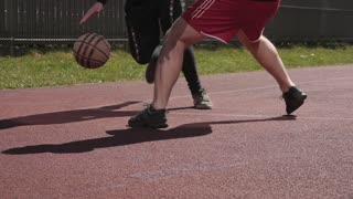 Two young active people guys play basketball game on a street sports ground