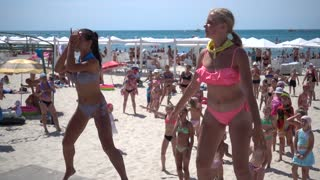 Two young Girls Animators dancing on the Beach in bikini Swimsuits for many People