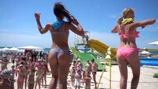 Two young Girls Animators dancing on the Beach in bikini Swimsuits for People