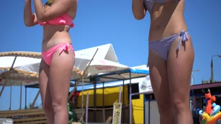Two young Girls Animators dancing on the Beach in bikini Swimsuits