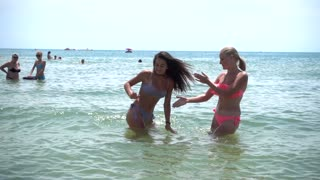 Two young Girls dancing in Water on the Sea Beach in bikini Swimsuits