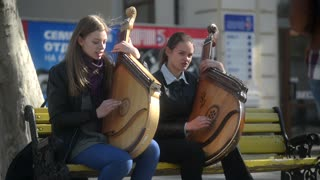 Two young girls play outdoors on Ukrainian bandura - street music