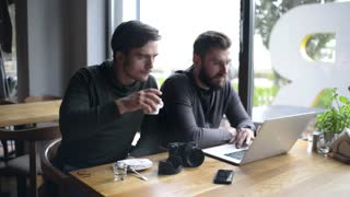 Two young Men Businessman sitting with Laptop and Mobile Gadgets at Cafe Table