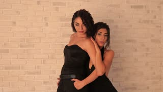 Two young Women Models Posing black Dress For Fashion Photo Session in Studio