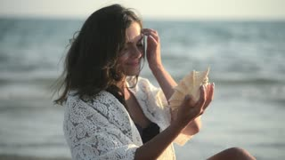 Woman Brunette with a big beautiful Seashell near the Face