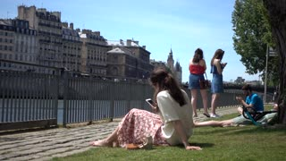 Woman chatting with Mobile Phone sitting relax near Seine in Paris