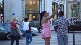 Woman make Selfie Foto against Showcase Louis Vuitton on Champs Elysees in Paris