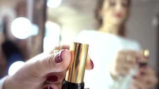Woman opens a red Lipstick against the Mirror - close-up