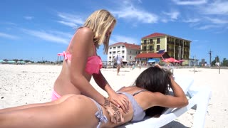 Woman relaxing on the beach chair taking Massage from a Girlfriend