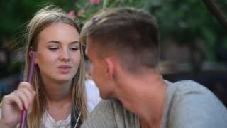 Woman smokes Hookah and Kiss her Boyfriend in Street Bar