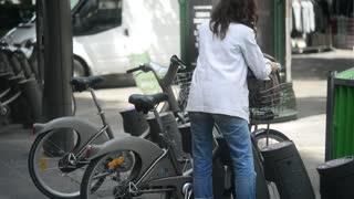 Woman take public transport bicycle in Center of Paris