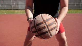 Young active Man guy plays basketball game on a street sports ground