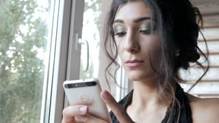 Young Brunette Woman use Mobile Smart Phone by the Window at Home