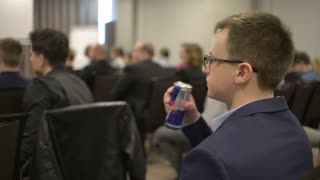 Young Business Man drinks Red Bull energy Drink in the Conference Room