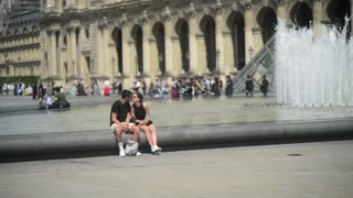 Young couple romantic kissing near fountain and Museum Louvre in city Paris