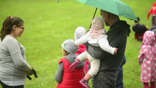 Young Father holds his child under Umbrella in rainy Park - Wroclaw, Poland
