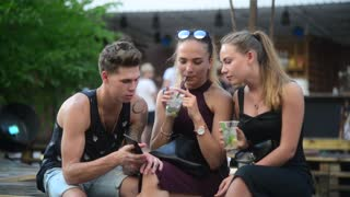 Young Friends Boy and Girl talk funny browse Mobile Phone in Bar with Cocktails