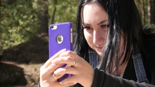 Young Girl Brunette make Photo with iPhone Mobile in Forest Nature Park - Summer