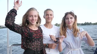 Young Girls and Boy Teenagers dancing together on a River Yacht