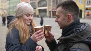 Young Guy and Girl Friends enjoy to look eyes to eyes with Love and hot Tea in a Paper Cups on a street of Wroclaw
