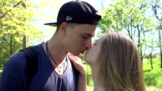 Young Guy and Girl kissing hugging on the green Grass in summer Park