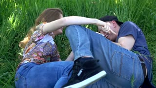 Young Guy and Girl lying happy on the green Grass in summer Park