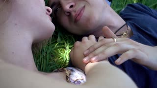 Young Guy and Girl lying on the green Grass in summer Park