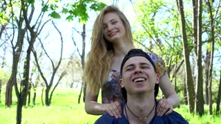 Young Guy and Girl relax having fun on the green Grass in summer Park