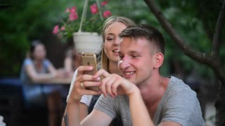 Young Guy and Girl sitting have fun with iphone Mobile browse Photos in network