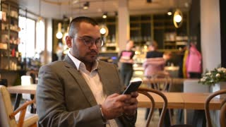 Young indian Businessman sit use Mobile Smart Phone in a cozy Cafe