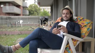 Young Latin Guy use Mobile Smart Phone to Communicate sitting at Home Backyard