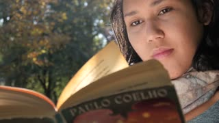 Young Latin Woman reading a Book sitting under the Tree in a Park