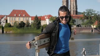 Young Latino Man standing with Skateboard smiling on the Quay in the City - Day