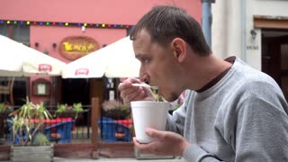 Young Man Guy Eating Chewing Soup meal In City Wroclaw Street - Poland