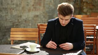 Young Man in a black Coat sitting alone at the Table Cafe with glossy Magazine