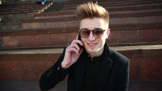 Young Man in Black Coat and Sunglasses talk to Mobile Phone in the Street Kiev
