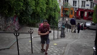 Young Man Photographer with photo camera walking up the Stairs Montmartre Paris