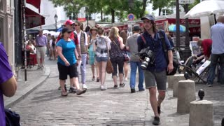 Young Man Photographer with video camera walking crowded Street Montmartre Paris
