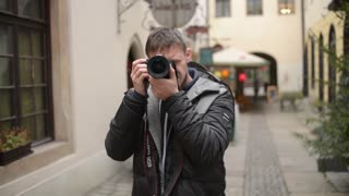 Young Man Photographer works in open Air in the City Street with Camera Canon