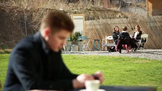 Young Man sitting alone at the Table Cafe looks at the Woman at the other Table