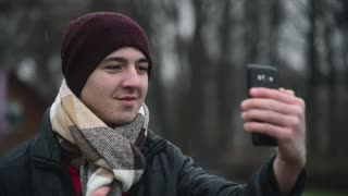 Young Man take Selfie Photo with Mobile Smart Phone on a Lake in winter Park
