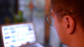 Young Man with Glasses work with Laptop with tired Eyes