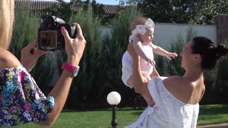 Young Mother lift up her little Baby Girl for Photographer Photo Session