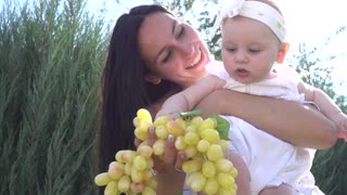 Young Mother take her little Baby Girl in Hands happy play with a Bunch of Grape
