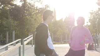 Young People Friends Guy and Girl talking in the Park, evening yellow Sun