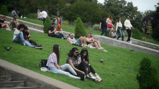 Young People relax sitting on the green Grass - Montmartre Paris